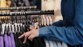 Vrouw die kleren op het rek kiezen stock video