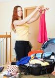 Vrouw die kleren toevoegt in koffers Stock Foto's