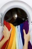 Vrouw die kleurenkleren van wasmachine neemt Stock Foto's