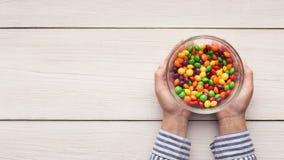 Vrouw die kleurrijk klein suikergoed in kom houden royalty-vrije stock afbeelding
