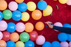Vrouw die kleurrijke ballons met een pijltje knallen stock foto