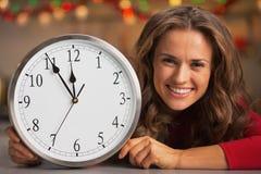 Vrouw die klok in Kerstmis verfraaide keuken tonen Royalty-vrije Stock Afbeeldingen