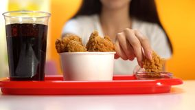 Vrouw die knapperige gebraden kippenvleugels in de close-up van de ketchupsaus, knapperige snack onderdompelen royalty-vrije stock foto's