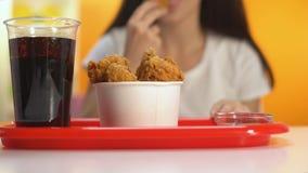 Vrouw die knapperige gebraden kippenvleugels in de close-up van de ketchupsaus, knapperige snack onderdompelen stock videobeelden
