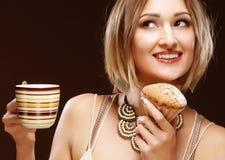 Vrouw die koekje eet en koffie drinkt royalty-vrije stock afbeeldingen