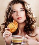 Vrouw die koekje eten en koffie drinken. stock afbeelding