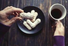 Vrouw die koekjes eten en hete drank drinken stock fotografie