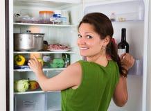 Vrouw die in koelkast kijken royalty-vrije stock foto's