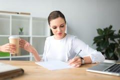Vrouw die koffie in document kop geven stock afbeeldingen