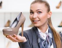 Vrouw die koffie-gekleurde hoog gehielde schoen houden royalty-vrije stock afbeelding