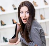 Vrouw die koffie-gekleurde modieuze schoen houden royalty-vrije stock afbeelding