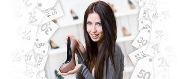 Vrouw die koffie-gekleurde schoen houden De zwarte Verkoop van de Vrijdag stock afbeelding