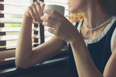 Vrouw die koffie hebben door het venster in diner Royalty-vrije Stock Foto's