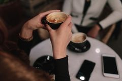 Vrouw die koffie met een vriend hebben bij koffie Royalty-vrije Stock Afbeeldingen