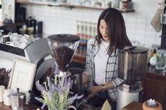 Vrouw die koffie met machine in koffie voorbereiden stock foto's
