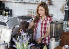 Vrouw die koffie met machine in koffie voorbereiden stock afbeeldingen