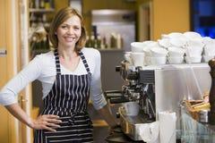 Vrouw die koffie in restaurant het glimlachen maakt Stock Afbeeldingen