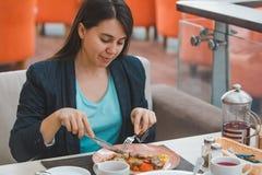 Vrouw die in koffie van stadswandelgalerij eten royalty-vrije stock afbeeldingen