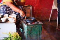 Vrouw die koffie voor toeristen op een traditionele manier voorbereiden royalty-vrije stock afbeeldingen