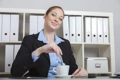 Vrouw die koffiepauze in bureau hebben Royalty-vrije Stock Fotografie
