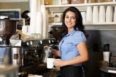 Vrouw die in koffiewinkel werkt Stock Foto