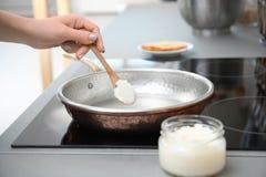 Vrouw die kokosnotenolie op pan in keuken zetten royalty-vrije stock foto's