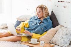 Vrouw die kop van koffie hebben en thuis met laptop werken stock foto's