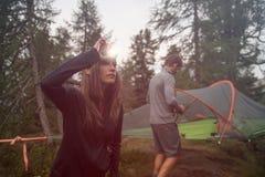 Vrouw die koplampflitslicht aanzetten die dichtbij tent het kamperen hangen Groep de reis van het de zomeravontuur van vriendenme Royalty-vrije Stock Foto's