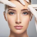 Vrouw die kosmetische botox injectie in voorhoofd krijgen stock afbeelding
