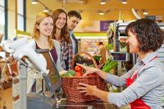 Vrouw die kruidenierswinkels betalen bij stock foto