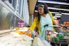 Vrouw die in kruidenierswinkelsectie winkelen royalty-vrije stock fotografie