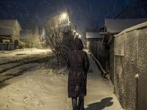 Vrouw die langs de straat in de avond lopen sneeuwval Royalty-vrije Stock Afbeelding