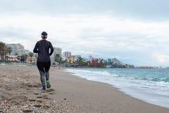 Vrouw die langs het strand op een promenade met zwarte kleren lopen stock afbeeldingen