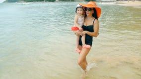 Vrouw die langs kustlijn met babymeisje lopen stock video