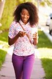 Vrouw die langs Straat aan het Werk lopen die aan Muziek luisteren stock fotografie