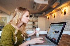 Vrouw die laptop computer in koffie met behulp van Royalty-vrije Stock Foto's