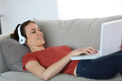 Vrouw die laptop en hoofdtelefoons op laag met behulp van royalty-vrije stock foto's