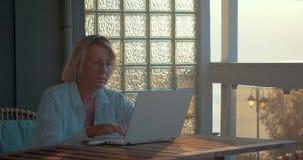 Vrouw die laptop en mobiel Internet-apparaat met behulp van stock videobeelden