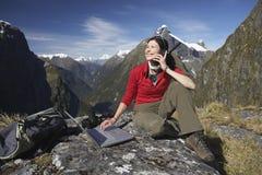 Vrouw die Laptop en Walkie-talkie met behulp van tegen Bergen stock afbeeldingen