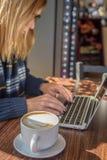 vrouw die laptop in koffiewinkel met behulp van met latte Stock Foto