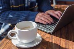 vrouw die laptop in koffiewinkel met behulp van met latte Royalty-vrije Stock Foto's