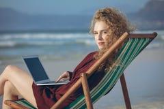 Vrouw die laptop met behulp van terwijl het zitten op zonlanterfanter bij strand stock fotografie