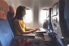 Vrouw die laptop met behulp van terwijl in vliegtuig dichtbij venster zit stock foto's