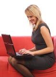 Vrouw die laptop op bank met behulp van Royalty-vrije Stock Foto