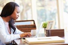 Vrouw die Laptop op Bureau thuis met behulp van royalty-vrije stock fotografie