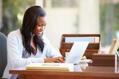 Vrouw die Laptop op Bureau thuis met behulp van royalty-vrije stock afbeeldingen