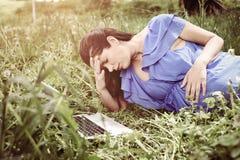 Vrouw die laptop op de weide met behulp van Vrouw die contract hebben Royalty-vrije Stock Fotografie