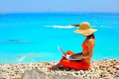 Vrouw die laptop op het strand met behulp van royalty-vrije stock afbeelding