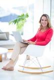Vrouw die laptop op schommelstoel met behulp van stock foto