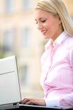 Vrouw die laptop in openlucht met behulp van royalty-vrije stock foto